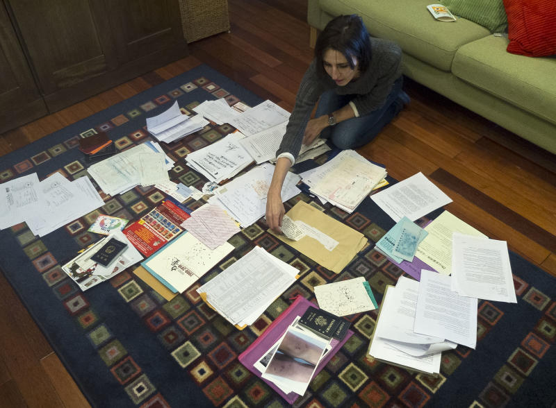 In this Feb. 17, 2012 photo, Kim Lee arranges documents to be submitted to court for her divorce case at her sister-in-law's house in Beijing, China. In past interviews on TV and on his microblog, Li Yang has confessed publicly to beating his wife, Kim Lee. Lee's case has opened the door to a torrent of anguish about domestic violence in her adopted country and she has became a folk hero for battered Chinese women. In China, where tradition holds that family matters are private and women are in many ways subservient to their husbands, the American woman's case has spawned tens of thousands of postings on Twitter-like sites, along with protests and talk show debates. It is especially explosive because she is a foreigner, at a time when China is particularly sensitive about how it is understood and treated by the world. (AP Photo/Andy Wong)