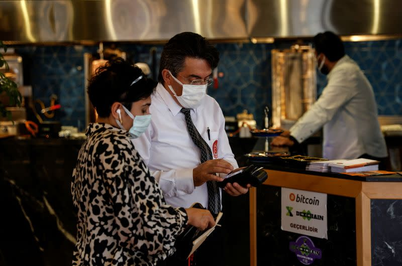 A customer makes payment at a restaurant in Istanbul