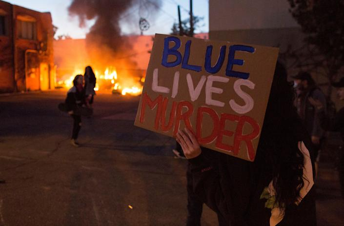 """<i>A protester holds a sign that says """"Blue Lives Murder"""" on May 29 in Minneapolis.</i>"""