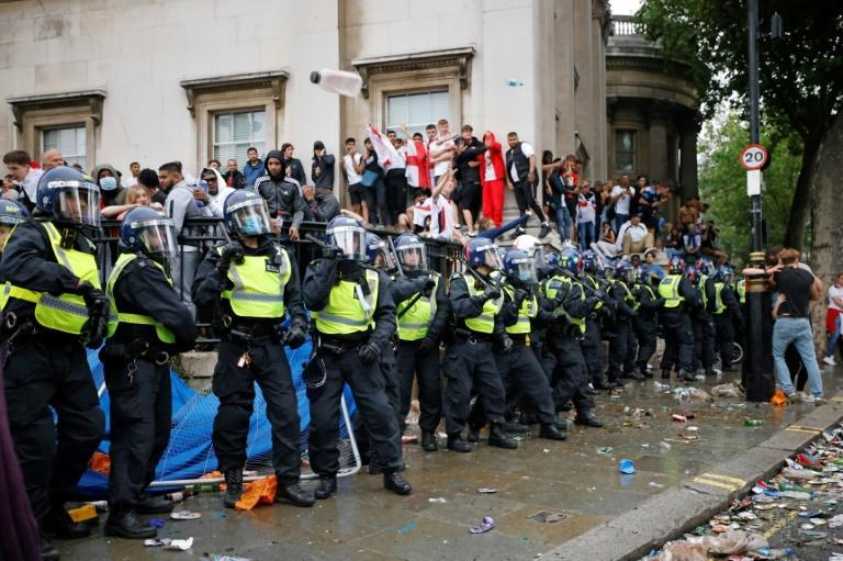 Police officers monitor England supporters standing on the edge of Trafalgar Square during a live screening of the UEFA EURO 2020 final