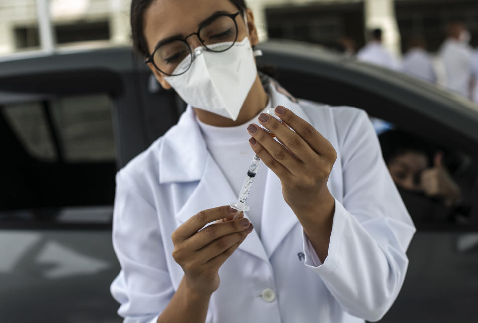 A healthcare worker prepares a dose of the China's Sinovac Biotech COVID-19 vaccine at a drive-thru vaccination site in the Sambadrome, in Rio de Janeiro, Brazil, Saturday, Feb. 6, 2021. In a normal year, Rio's Sambadrome would be preparing for its great moment of the year: the world's most famous Carnival parade. But a week before what should be the start of Carnival, the pandemic has replaced pageantry. (AP Photo/Bruna Prado)