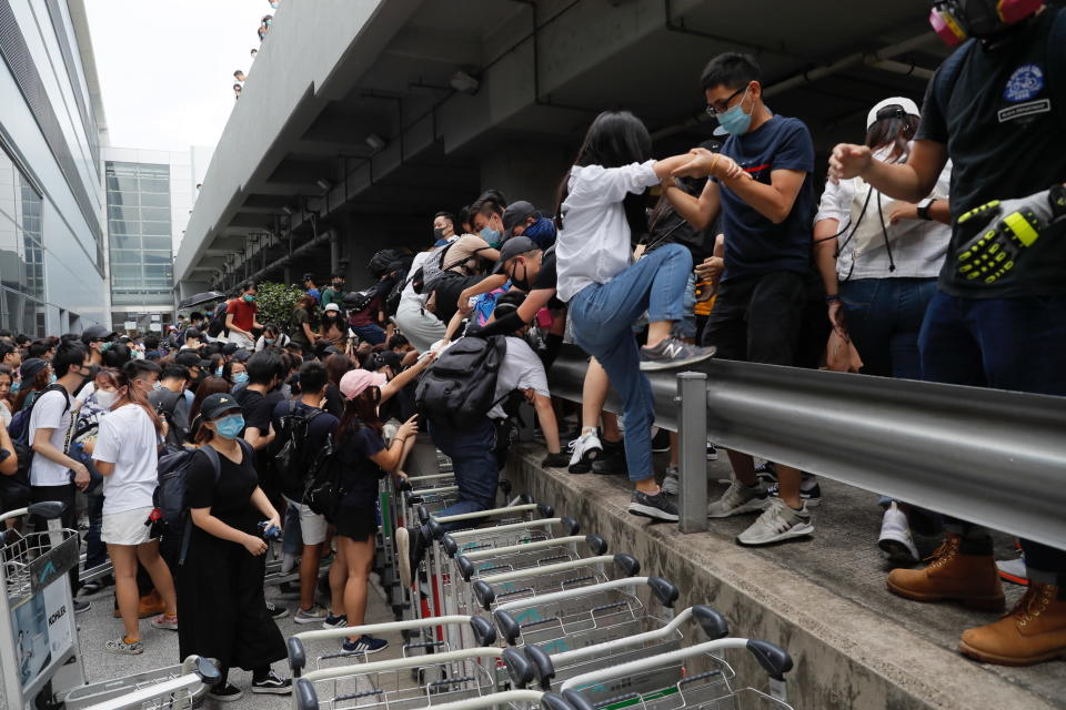 Pro-democracy protestors leave after riot police arrive outside the airport in Hong Kong, Sunday, Sept.1, 2019. Train service to Hong Kong's airport was suspended Sunday as pro-democracy demonstrators gathered there, while protesters outside the British Consulate called on London to grant citizenship to people born in the former colony before its return to China. (AP Photo/Kin Cheung)