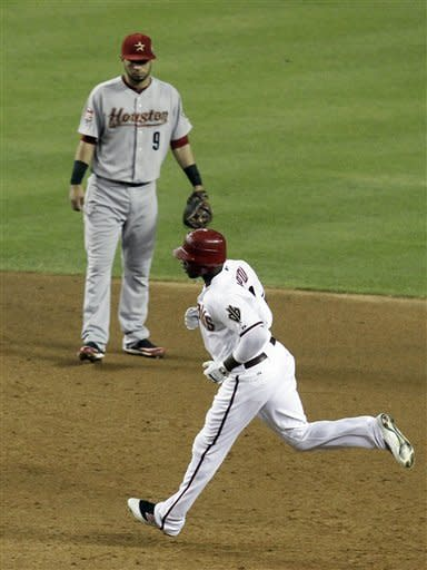 Arizona Diamondbacks' Justin Upton, bottom, rounds the bases after hitting a two-run home run as Houston Astros' Marwin Gonzalez (9) looks on during the third inning in a baseball game on Friday, July 20, 2012, in Phoenix. (AP Photo/Ross D. Franklin)