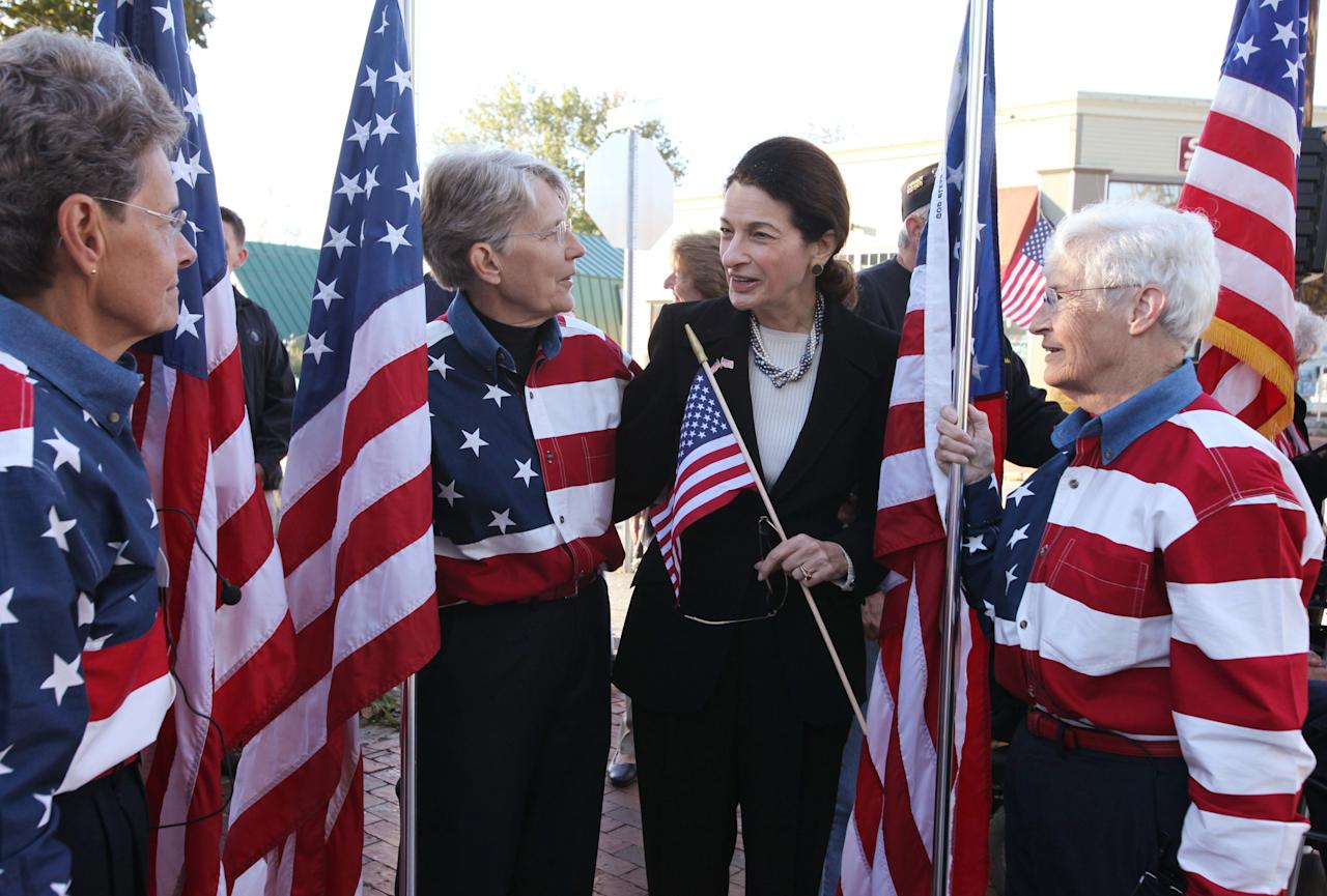 Freeport Flag Ladies Carmen Footer, left, Elaine Green, center, and JoAnn Miller, right, speak with Sen. Olympia Snowe, R-Maine, as they gather Sunday, Sept. 11, 2011 on Main St. in Freeport, Maine to mark the 10th anniversary of 9/11. (AP Photo/Joel Page)