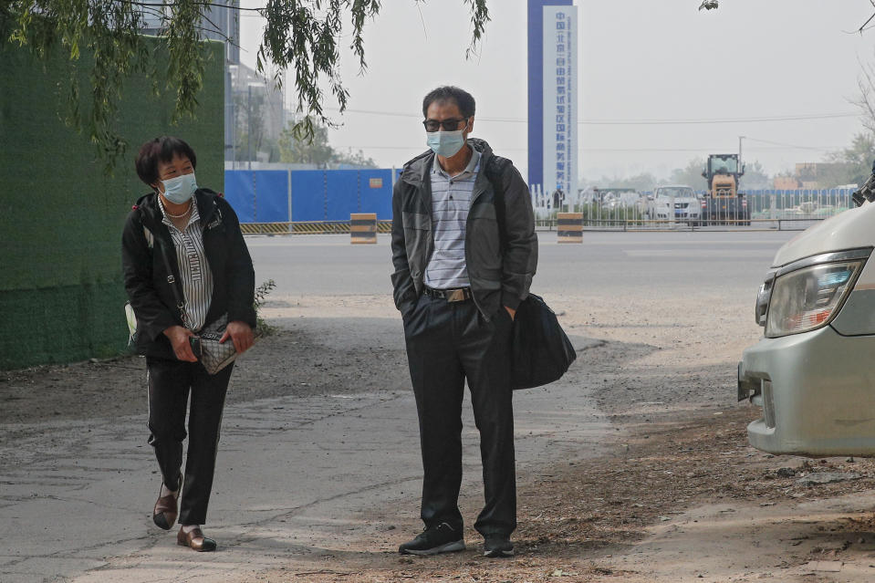 Wei Xiuwen, left, mother of Chen Mei, and Cai Jianli, center, father of Cai Wei arrive outside a courthouse to attend their children's court cases in Beijing, Tuesday, May 11, 2021. Two amateur computer coders taken by police from their Beijing homes last year were standing trial Tuesday in a case that illustrates the Chinese government's growing online censorship and heightened sensitivity to any deviation from the official narrative on its COVID-19 response. (AP Photo/Andy Wong)