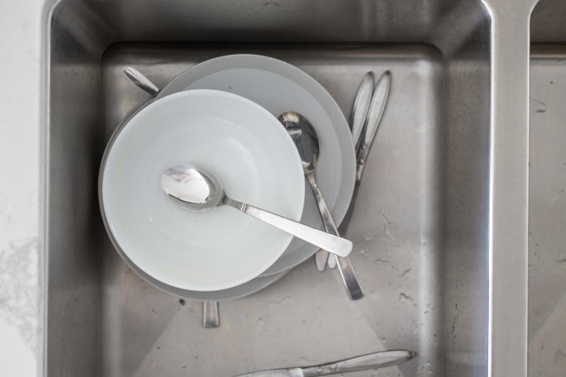 A sink filled with dirty plates, bowls and cutlery.