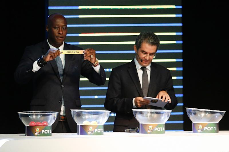 Fomer Senegalese football player Khalilou Fadiga (L) shows a piece of paper bearing the name of Ouganda next to Confederation of African Football (CAF) secretary general Hicham El Amrani during the 2017 African Cup of Nations draw ceremony (AFP Photo/Marco Longari)
