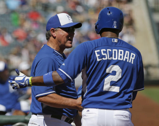 Kansas City Royals manager Ned Yost greets Alcides Escobar after he scored during the second inning of a spring exhibition baseball game against the Texas Rangers, Saturday, March 22, 2014, in Surprise, Ariz. (AP Photo/Darron Cummings)