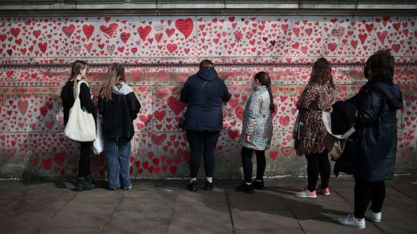 PHOTO: People stand by the National Covid Memorial wall beside St Thomas' hospital set as a memorial to all those who have died so far in the U.K. from the coronavirus disease, in London, April 8, 2021. (Hannah Mckay/Reuters)