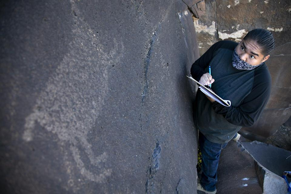 Zion White, a tribal member of the Fort Yuma Quechan Indian Tribe, sketches petroglyphs near the Gila River in an area of Bureau of Land Management public land known as the Great Bend of the Gila on Feb. 3, 2021.