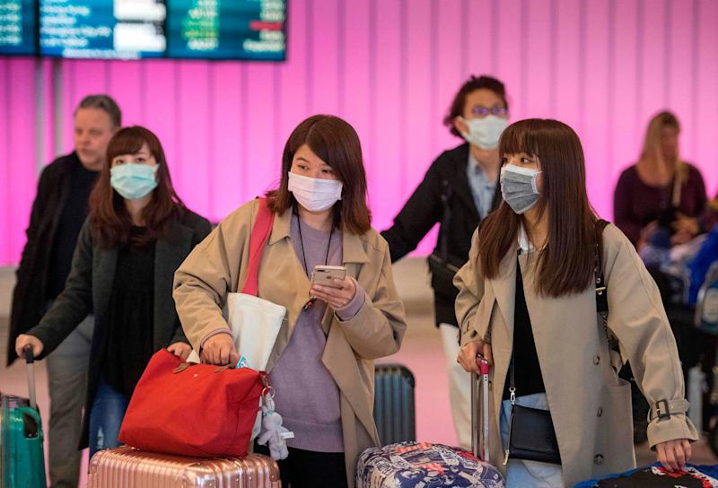 Passengers wear protective masks to protect against the spread of the Coronavirus as they arrive at the Los Angeles International Airport, California: AFP via Getty Images