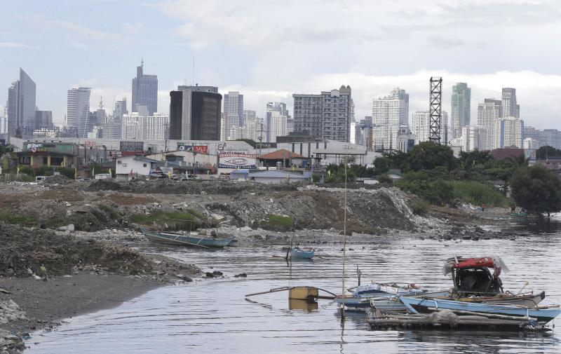 In this Tuesday July 2, 2013 photo, construction is in progress at a reclamation site on Manila Bay amidst buildings in the background. As the Philippine economy skyrocketed 7.8 percent in the first quarter, outpacing China, the middle class in the Southeast Asian nation that has been held back by widespread poverty, political strife and corruption is for the first time in decades reaping the profits of an economic boom. (AP Photo/Bullit Marquez)