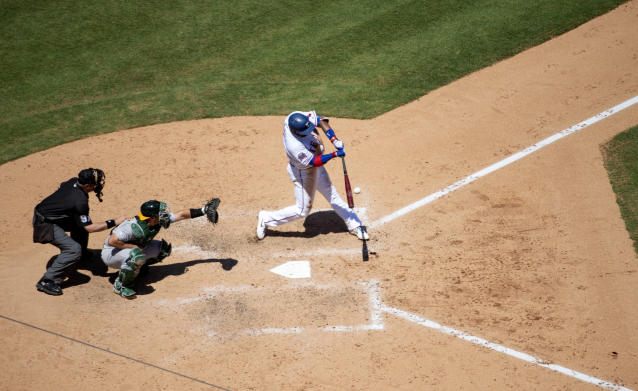 Texas Rangers' Elvis Andrus connects for a double off of Oakland Athletics relief pitcher Ryan Dull as catcher Josh Phegley and home plate umpire Brian Knight look on during the fifth inning of the first baseball game of a doubleheader Saturday, June 8, 2019, in Arlington, Texas. (AP Photo/Jeffrey McWhorter)
