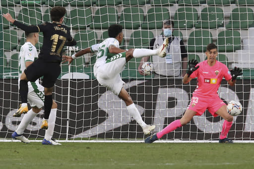 Elche's goalkeeper Edgar Badia fails to save a shot by Barcelona's Riqui Puig, not seen, who scored his side's second goal during the Spanish La Liga soccer match between Elche and Barcelona at the Manuel Martinez Valero stadium in Elche, Spain, Sunday, Jan. 24, 2021. (AP Photo/Alberto Saiz)