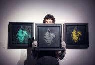 A gallery assistant poses with artwork titled 'Three Self-Portraits' by Andy Warhol, during a photocall at Christie's auction house, in London