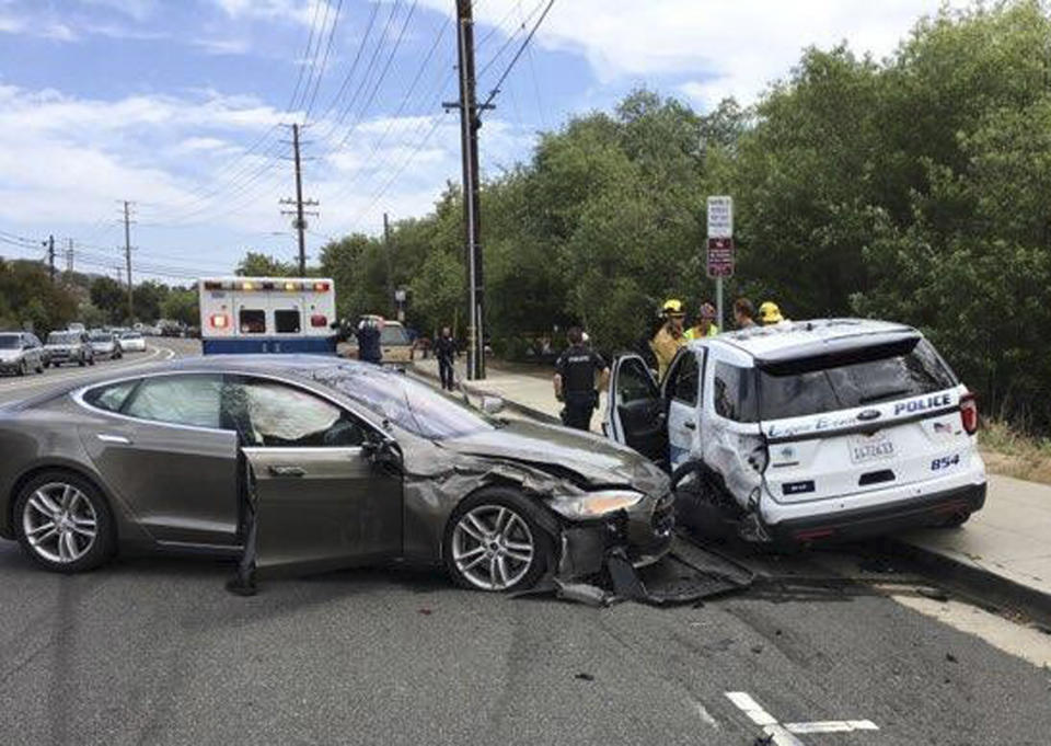 This photo provided by the Laguna Beach Police Department shows a Tesla sedan, left, in autopilot mode that crashed into a parked police cruiser Tuesday, May 29, 2018, in Laguna Beach, Calif. Police Sgt. Jim Cota says the officer was not in the cruiser at the time of the crash and that the Tesla driver suffered minor injuries. (Laguna Beach Police Department via AP)