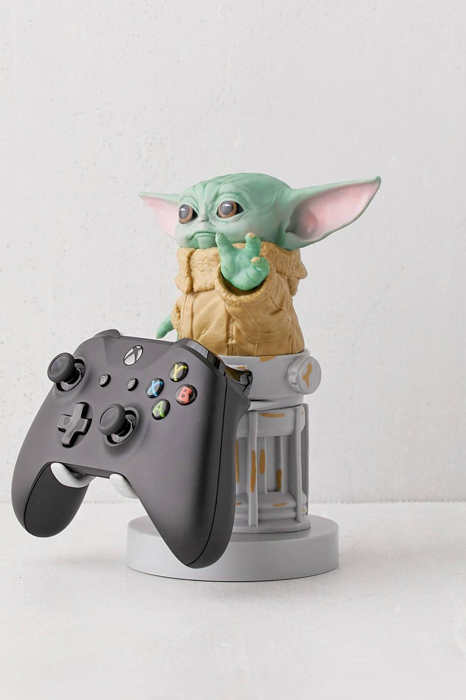 """With Baby Yoda guarding his favorite controller, he'll never have to worry about it getting misplaced again. <br><br><strong>Cable Guys</strong> The Child Device Holder, $, available at <a href=""""https://go.skimresources.com/?id=30283X879131&url=https%3A%2F%2Fwww.urbanoutfitters.com%2Fshop%2Fcable-guys-the-child-device-holder%3Fcategory%3Dgifts-for-men%26color%3D030%26type%3DREGULAR%26size%3DONE%2520SIZE%26quantity%3D1"""" rel=""""nofollow noopener"""" target=""""_blank"""" data-ylk=""""slk:Urban Outfitters"""" class=""""link rapid-noclick-resp"""">Urban Outfitters</a>"""