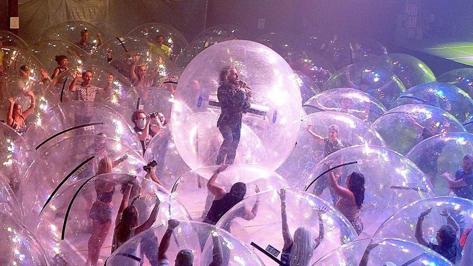 The Flaming Lips perform to audience members in bubbles