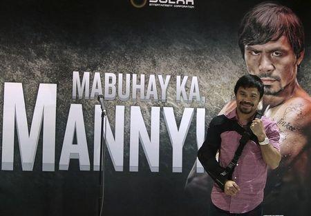 Boxer Manny Pacquiao poses for the members of the media upon his arrival at the international airport in Manila May 13, 2015. REUTERS/Romeo Ranoco
