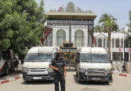 Police cars and a military armored personnel carrier block the entrance of the Tunisian parliament in Tunis, Tuesday, July 27, 2021. The Ennahda party, has called for dialogue, following President Kais Saeid's sacking of the prime minister and suspension of parliament on Sunday. (AP Photo/Hassene Dridi)