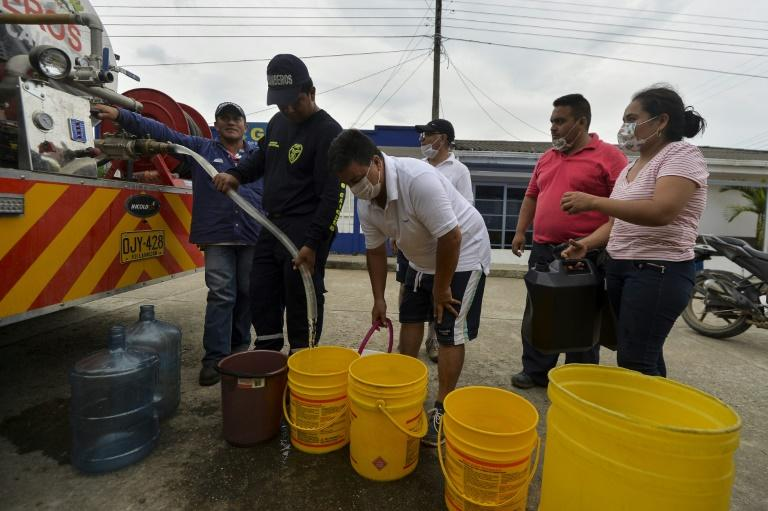 People collect water in Mocoa, on April 4, 2017 as the region struggles to recover from a devatating landslide