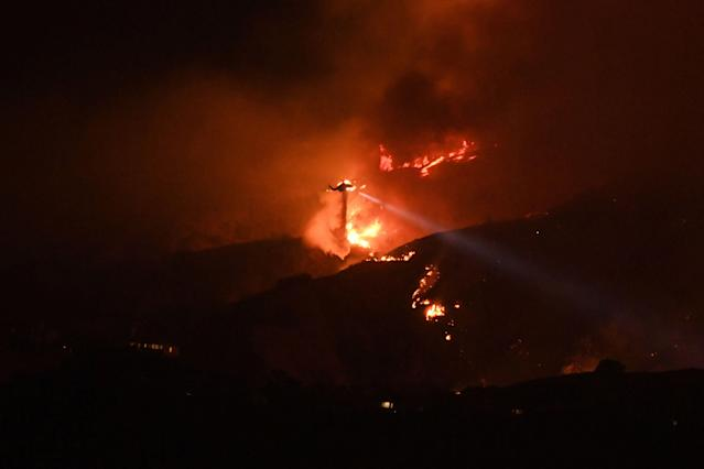 <p>A helicopter drops water on the La Tuna Canyon fire at night in the hills above Burbank, Calif., early Sept. 2, 2017. (Photo: Robyn Beck/AFP/Getty Images) </p>