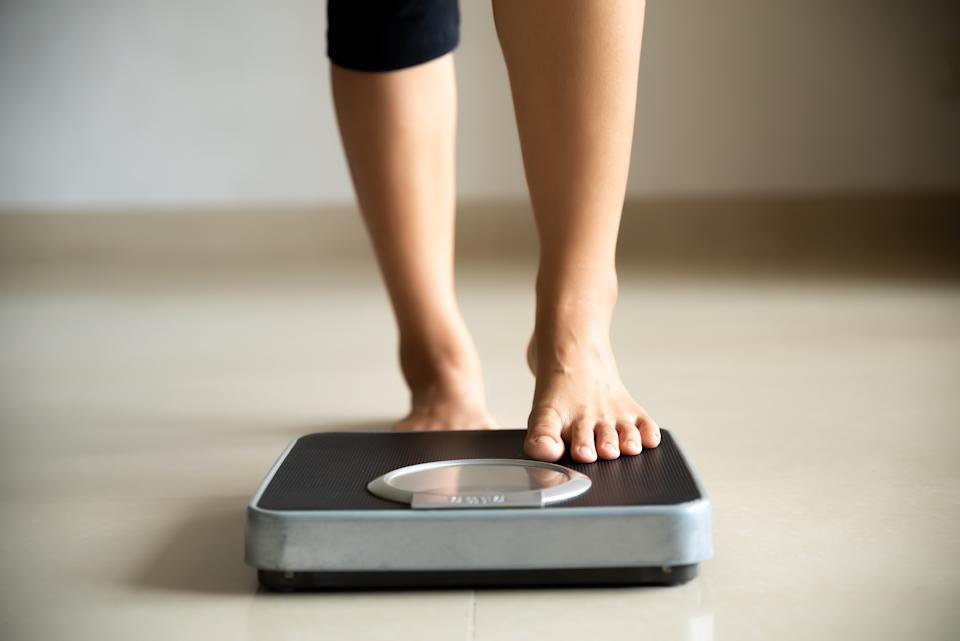 Female leg stepping on weigh scales. Healthy lifestyle, food and sport concept.