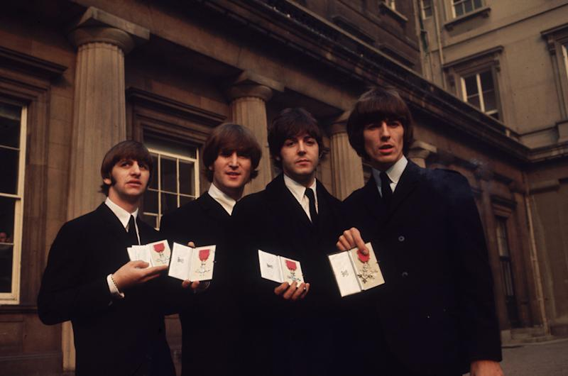 26th October 1965: British pop group The Beatles, from left to right; Ringo Starr, John Lennon (1940 - 1980), Paul McCartney and George Harrison (1943 - 2001), outside Buckingham Palace, London, after receiving their MBE's (Member of the Order of the British Empire) from the Queen.
