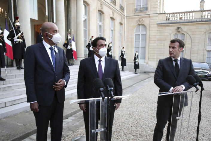 French President Emmanuel Macron, right, Mohammad Younes Menfi, president of Libya's Presidential Council, center, and Musa al-Koni, vice-president of Libya's Presidential Council, left, arrive to deliver a speech at the end of a meeting, at the Elysee Palace, in Paris, Tuesday, March 23, 2021. Macron said France will reopen its embassy in Libya's capital Tripoli on Monday as a gesture of support for the new interim government. (AP Photo/Thibault Camus)