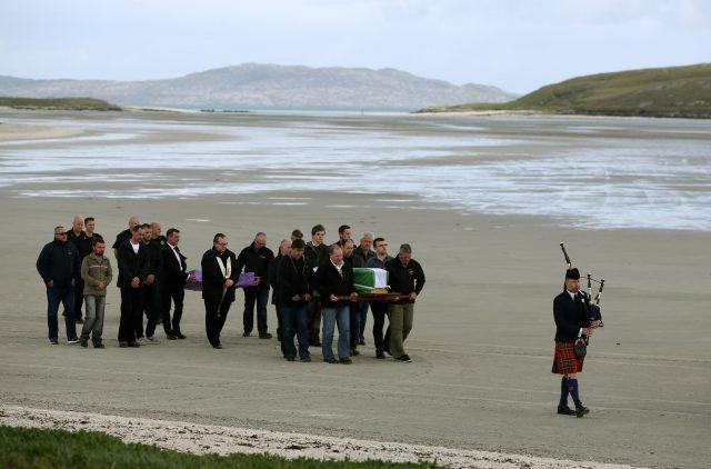 The coffin of Eilidh MacLeod draped in the Barra flag is carried across Traigh Mhor beach
