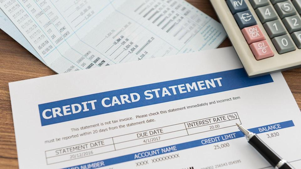 credit card statement with bank account, calculator on desk
