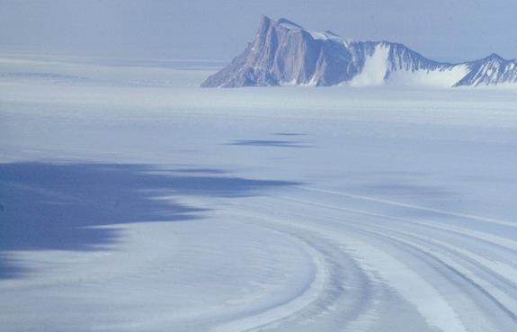 The West Antarctic ice sheet rests on a bed well below sea level and is drained by much larger outlet glaciers and ice streams that accelerate over large distances before reaching the ocean, often through large floating ice shelves.