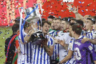 Real Sociedad's Mikel Oyarzabal, who scored the only goal, holds the cup as he celebrates with teammates after winning the final of the 2020 Copa del Rey, or King's Cup, soccer match between Athletic Bilbao and Real Sociedad at Estadio de La Cartuja in Sevilla, Spain, Saturday April 3, 2021. The game is the rescheduled final of the 2019-2020 competition which was originally postponed due to the coronavirus pandemic. (AP Photo/Angel Fernandez)