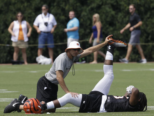 Cincinnati Bengals outside linebacker Vontaze Burfict stretches with the help of a trainer during the NFL football team's practice at training camp, Friday, July 25, 2014, in Cincinnati. (AP Photo)