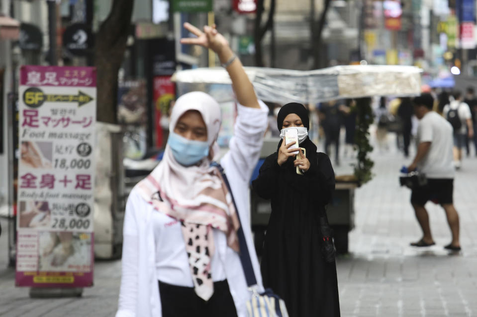 A woman wearing a face mask to help protect against the spread of the coronavirus takes photos of her friend at a shopping street in Seoul, South Korea, Wednesday, Aug. 5, 2020. (AP Photo/Ahn Young-joon)