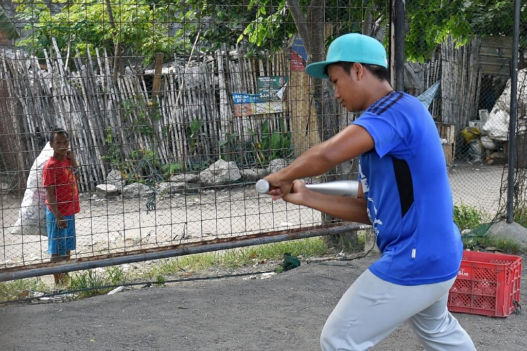 A trash pickerwatches as member of the Smokey Mountain baseball team trains at the former landfill in Manila (AFP Photo/Ted Aljibe)