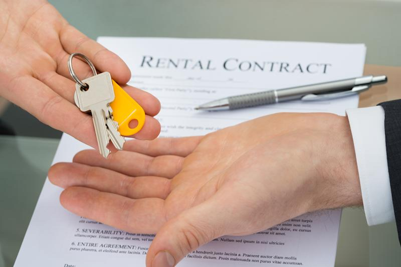 A person handing over keys, with a signed rental contract and pen on a table.