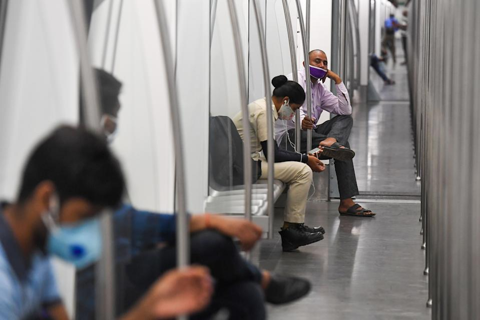 Commuters sit in a carriage of a Yellow Line train after Delhi Metro Rail Corporation (DMRC) resumed services following its closure due to the coronavirus pandemic in New Delhi on September 7, 2020. (Photo by PRAKASH SINGH/AFP via Getty Images)