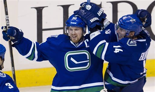 Vancouver Canucks center Henrik Sedin (33) celebrates his goal with Alex Burrows against the Edmonton Oilers during the second period of an NHL hockey game, Saturday, April, 7, 2012, in Vancouver, British Columbia. (AP Photo/The Canadian Press, Jonathan Hayward)