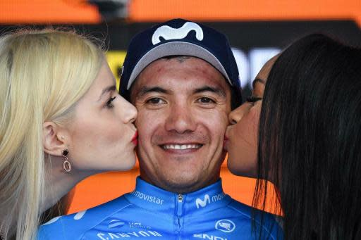 Ecuador's Richard Carapaz receives the kiss of the race's hostesses on the podium after winning the 4th stage of the Giro d'Italia, tour of Italy cycling race, from Orbetello to Frascati, Tuesday, May 14, 2019. Richard Carapaz of Ecuador sprinted to victory in the fourth stage of the Giro d'Italia on Tuesday, while Slovenian cyclist Primoz Roglic kept the overall lead after avoiding a crash toward the end of the route. (Alessandro Di Meo/ANSA via AP)