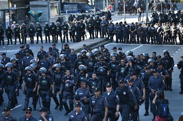 Riot police stand guard as demonstrators protest against the FIFA World Cup to demand better social services near the Maracana Stadium in Rio de Janeiro on July 13, 2014 (AFP Photo/Yasuyoshi Chiba)