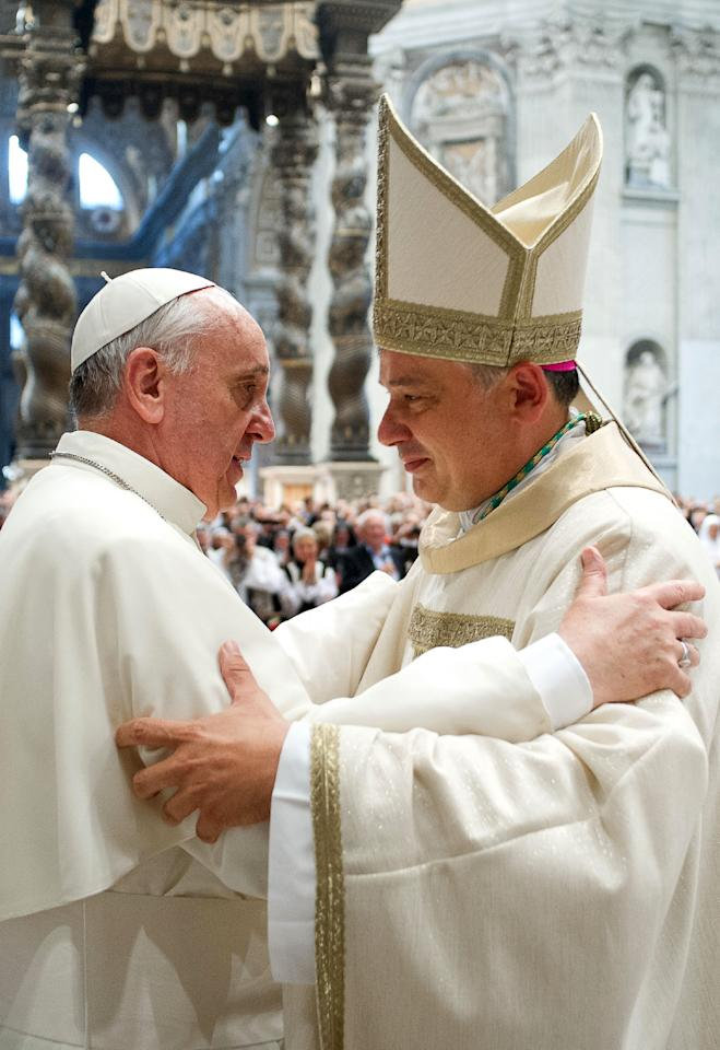 In this photo taken on Sept.19, 2013 provided by the Vatican newspaper L'Osservatore Romano, Pope Francis, left, hugs Vatican Almoner, Archbishop Konrad Krajewski, after his episcopal ordination, in St. Peter's Basilica, at the Vatican. The existence of the Vatican Almoner dates back centuries: It is mentioned in a papal bull from the 13th-century Pope Innocent III, and Pope Gregory X, who ruled from 1271-1276, organized it into an official Holy See office for papal charity. Up until Krajewski came along, the almoner was typically an aging Vatican diplomat who was serving his final years before being allowed to retire at age 75. Francis changed all that, tapping the 50-year-old Pole to be a more vigorous, hands-on extension of himself. The almoner's duties are two-fold: carrying out acts of charity, and raising the money to fund them. (AP Photo/L'Osservatore Romano, ho)