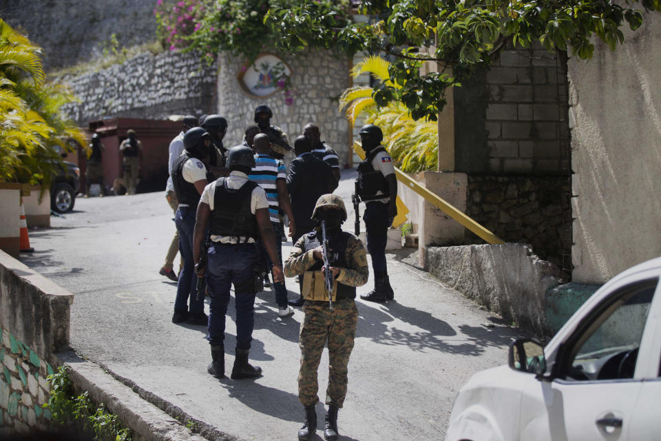 Security forces conduct an investigation as a soldier stands guard at the entrance to the residence of Haitian President Jovenel Moise.