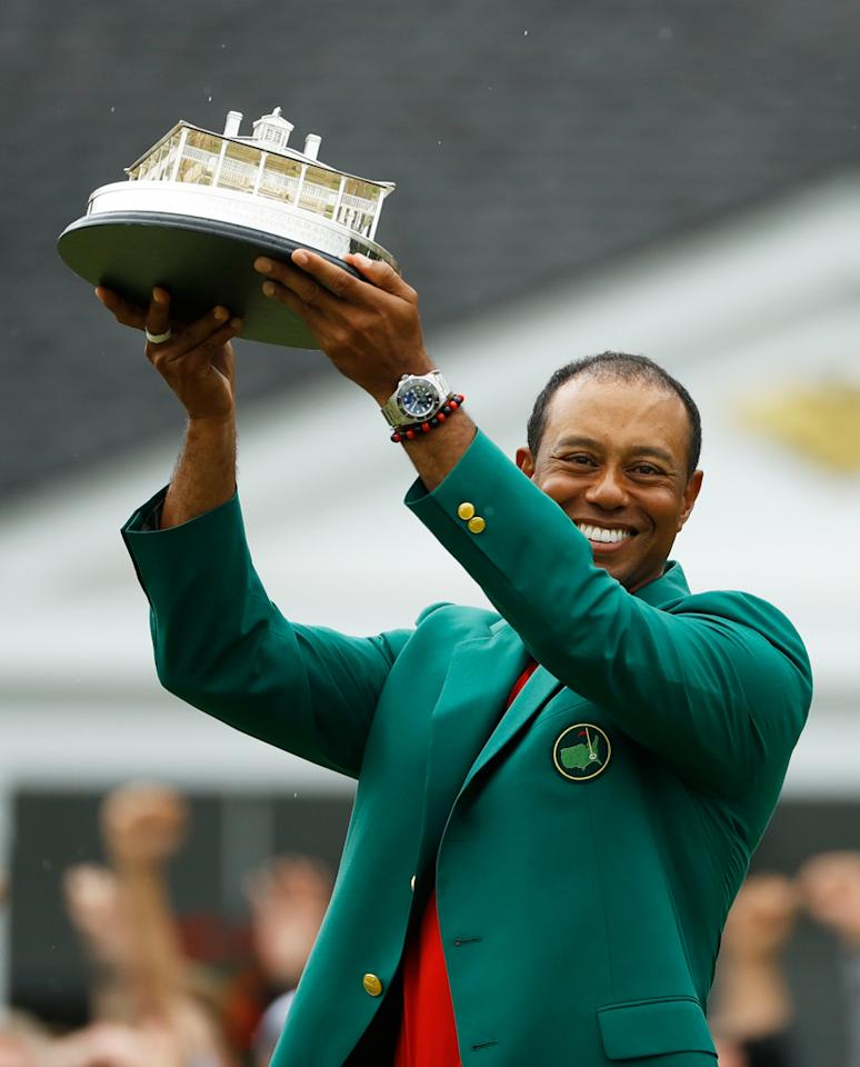 Tiger Woods wears his green jacket holding the winning trophy after the final round for the Masters golf tournament in Augusta, Georgia. (Image: AP)