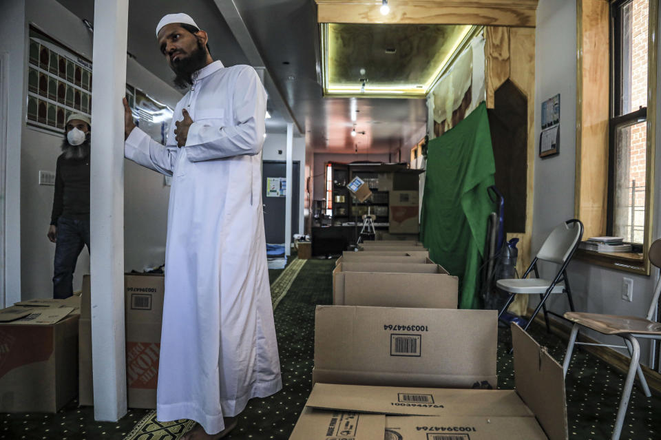 In this Wednesday, April 22, 2020, photo, Imam Mufti Mohammed Ismail, leader of An-Noor Cultural Center and masjid that serves a mostly Bangladeshi Muslim community in the Elmhurst neighborhood in the Queens borough of New York, stands near boxes of food for distribution to those impacted by COVID-19 restrictions. Ismail says this gives the center the opportunity to fulfill one of Ramadan's tenets — to serve those less fortunate, regardless of religion. (AP Photo/Bebeto Matthews)