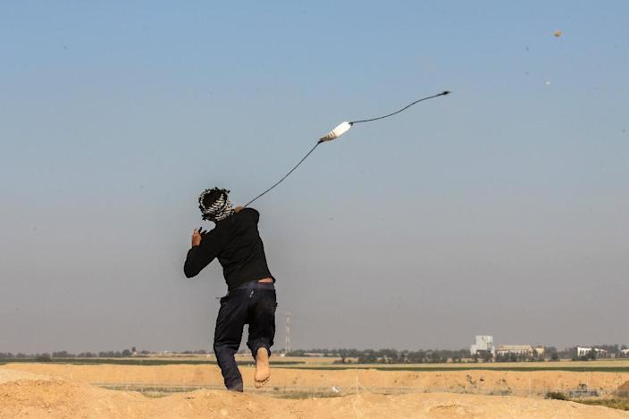 A Palestinian man swings a sling shot during clashes with Israeli security forces near the border with Israel, east of Khan Yunis, in the southern Gaza Strip, on April 01, 2018 (AFP Photo/SAID KHATIB)
