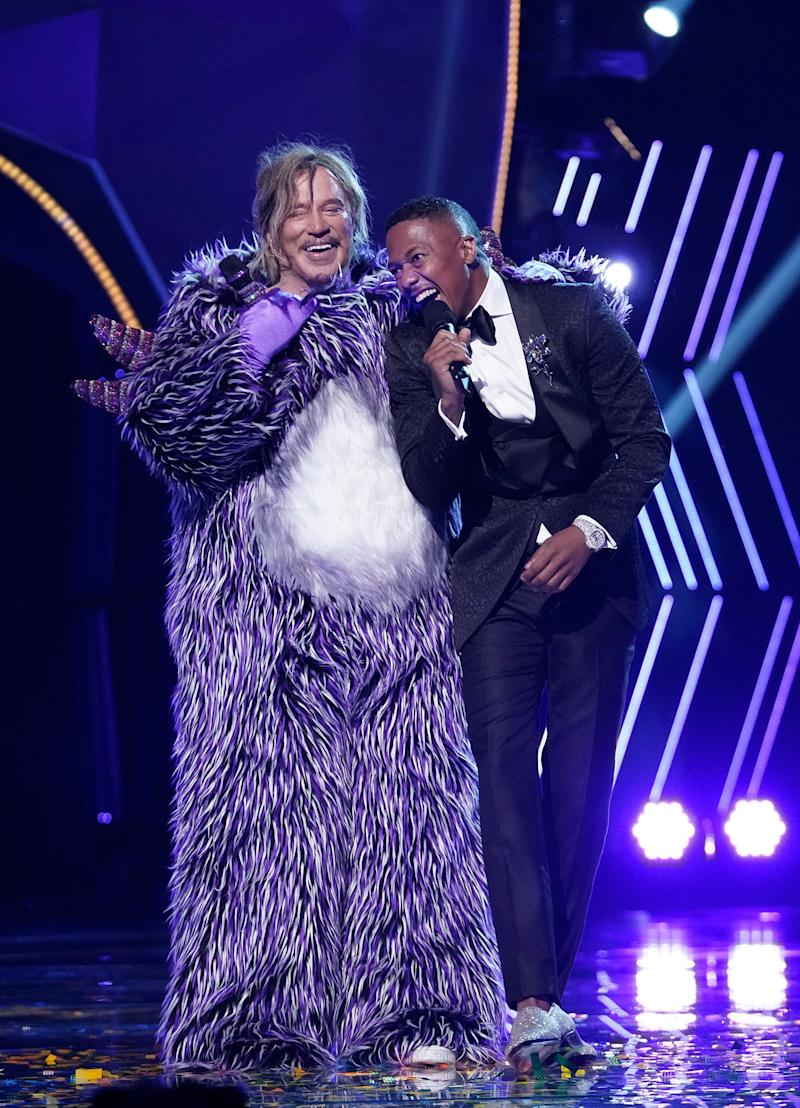 """Mickey Rourke and """"Masked Singer"""" host Nick Cannon have a laugh after the Oscar nominee removed his mask of his own volition."""
