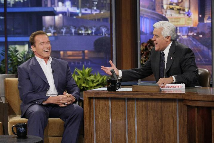 """This Oct. 8, 2012 photo released by NBC shows former California Gov. Arnold Schwarzenegger, left, is interviewed by host Jay Leno on """"The Tonight Show with Jay Leno"""" in Burbank, Calif. NBC has cut the salary of the popular late night talk show host in an an effort by new owner Comcast Corp., to reboot the network.  (AP Photo/NBC, Paul Drinkwater)"""