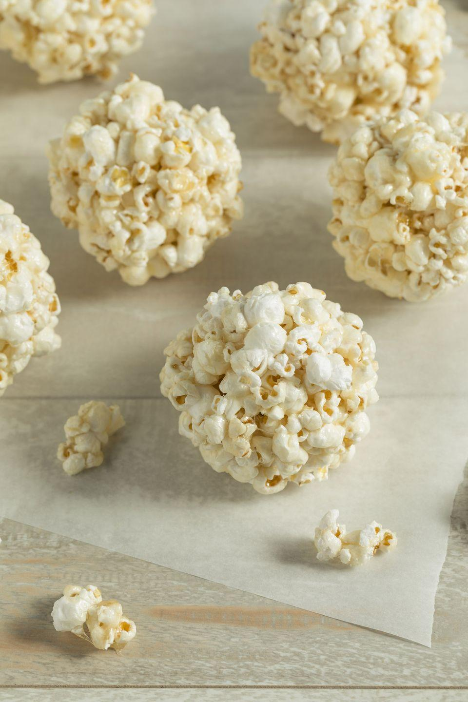 """<p>Mix in your favorite candies into these popcorn balls for an irresistibly sweet and sticky treat.</p><p><strong><a href=""""https://www.countryliving.com/food-drinks/recipes/a1973/sweet-popcorn-balls-clv1007/"""" rel=""""nofollow noopener"""" target=""""_blank"""" data-ylk=""""slk:Get the recipe"""" class=""""link rapid-noclick-resp"""">Get the recipe</a>.</strong></p>"""
