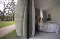 View of the bedroom showing the printer layers in the walls of the 3D-printed 94-square meters (1,011-square feet) two-bedroom bungalow resembling a boulder with windows in Eindhoven, Netherlands, Friday, April 30, 2021. The fluid, curving lines of its gray walls look natural. But they are actually at the cutting edge of housing construction in the Netherlands and around the world. They were 3D printed at a nearby factory. (AP Photo/Peter Dejong)